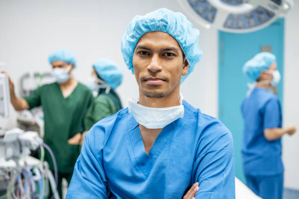 male surgeon in his 30s looking at camera with serious expression - surgeon стоковые фото и изображения