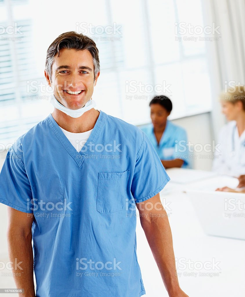 Male surgeon smiling with colleagues at the back royalty-free stock photo