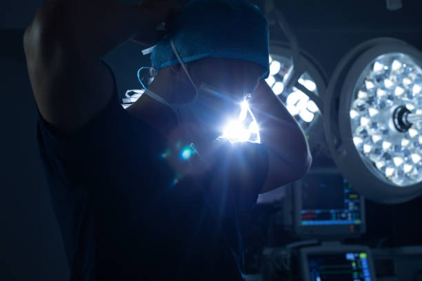 Male surgeon wearing surgical mask in operation theater stock photo