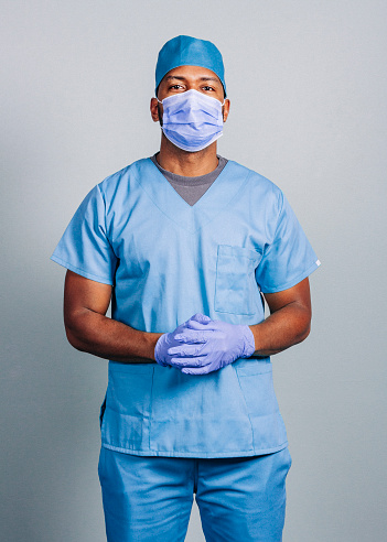 Confident surgeon in blue scrubs during COVID-19. Portrait of male nurse wearing protective workwear during pandemic. He is standing against gray background.