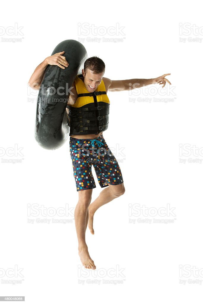 Male swimmer holding inner tube and jumping stock photo