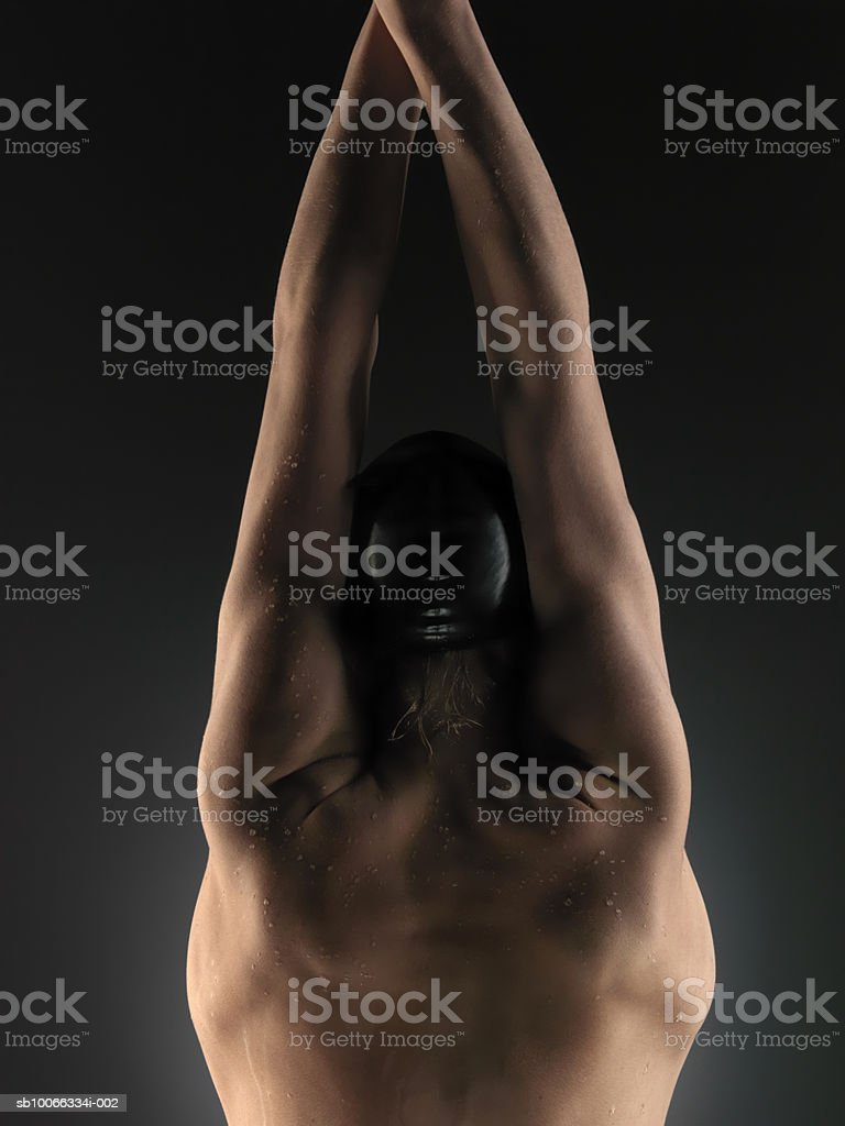 Male swimmer (16-17) on dark background with arms raised, rear view foto de stock libre de derechos