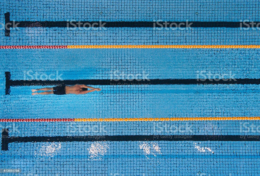 Male swimmer swimming laps in a pool Top view shot of young man swimming laps in a swimming pool. Male swimmer gliding through the water. Active Lifestyle Stock Photo