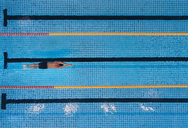male swimmer swimming laps in a pool - vuelta completa fotografías e imágenes de stock