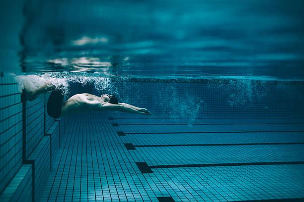 nadador masculino que se da la vuelta en la piscina - natación fotografías e imágenes de stock