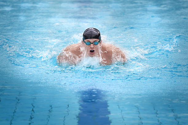 Male swimmer with a black cap performing butterfly stock photo