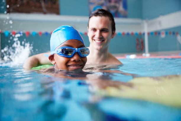 entrenador de natación masculino dando niño sosteniendo flotador de una a una lección en la piscina - natación fotografías e imágenes de stock