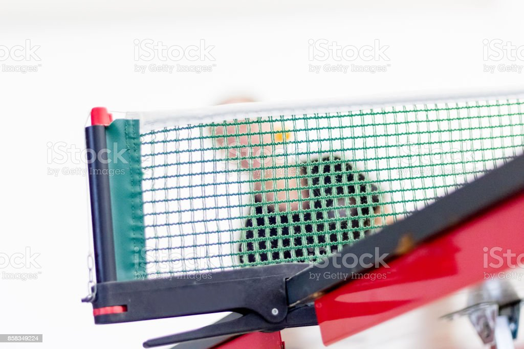 Male table tennis player playing forehand topspin. View through net, low section. Focus on net. stock photo