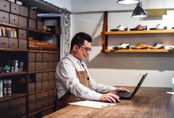 Männlicher taiwanesischer Schuhhändler arbeitet am Laptop – Foto