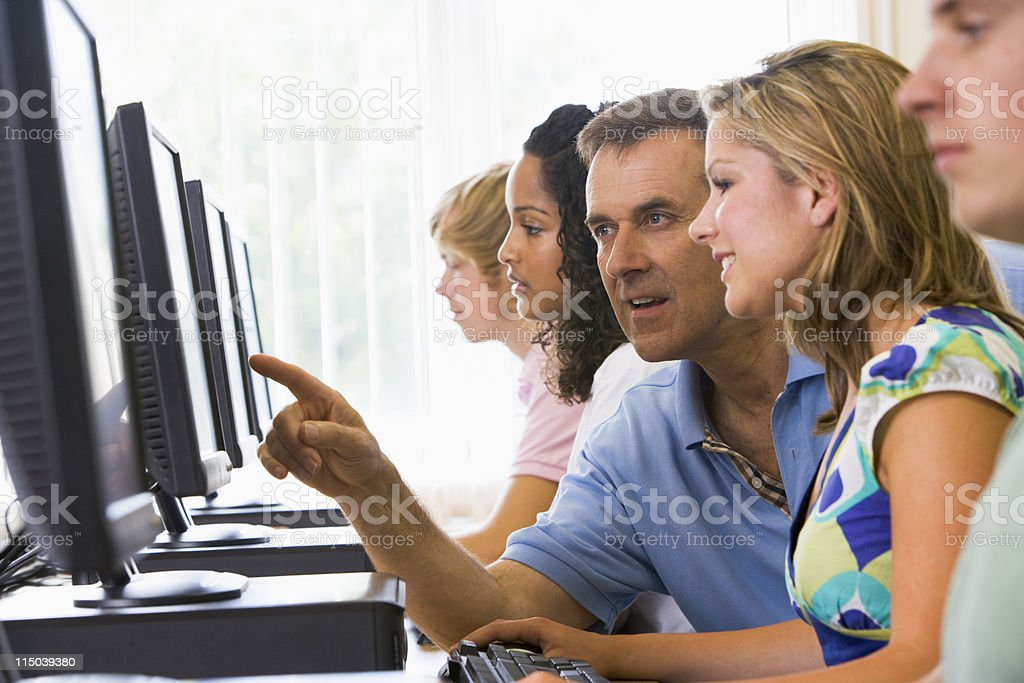 Male teacher assisting college student in a computer lab royalty-free stock photo