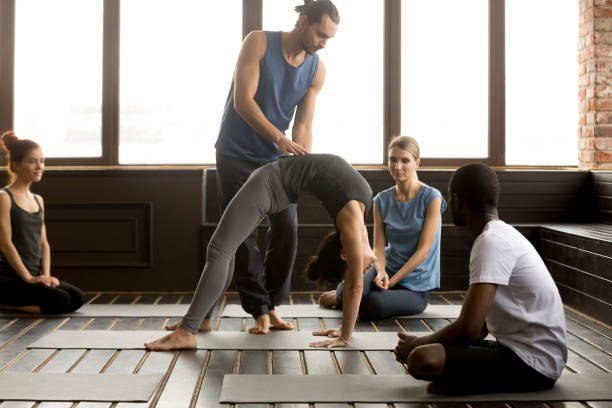Male teacher assisting woman doing yoga bridge exercise on mat Male teacher assisting young woman doing yoga exercise on mat, instructor helping flexible girl performing bridge pose, urdhva dhanurasana or chakrasana at group training class with diverse people upward facing dog position stock pictures, royalty-free photos & images