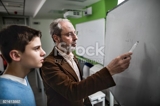 911029590 istock photo Male teacher explaining a lesson to high school student. 521613552