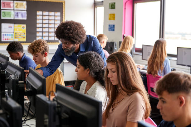 male teacher helping teenage female high school student working in computer class - high school teacher stock pictures, royalty-free photos & images
