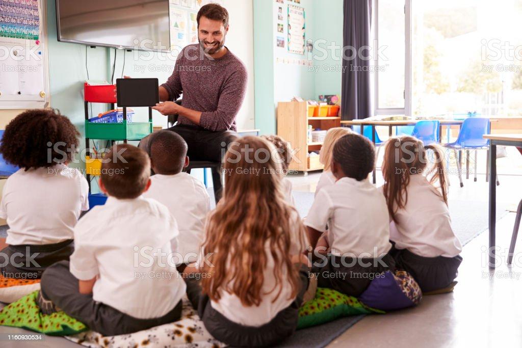Male Teacher Holding Digital Tablet Teaches Group Of Uniformed...