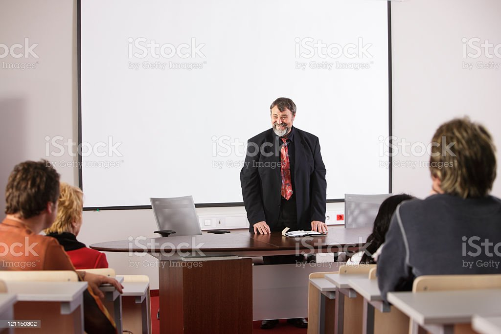 Male teacher in front of mixed aged students stock photo