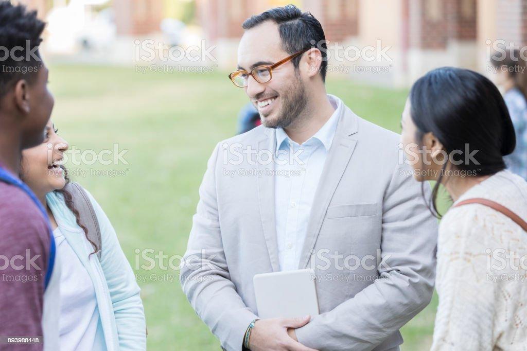Hispanic male high school teacher or principal talks with a group of...