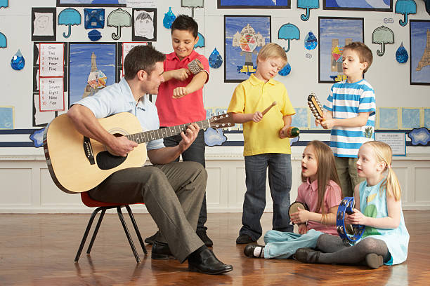 Male Teacher Playing Guitar With Pupils Having Music Lesson stock photo