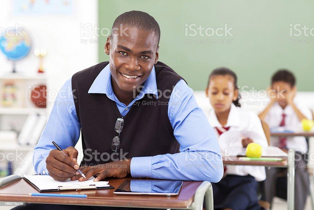 male teacher preparing lesson in classroom stock photo