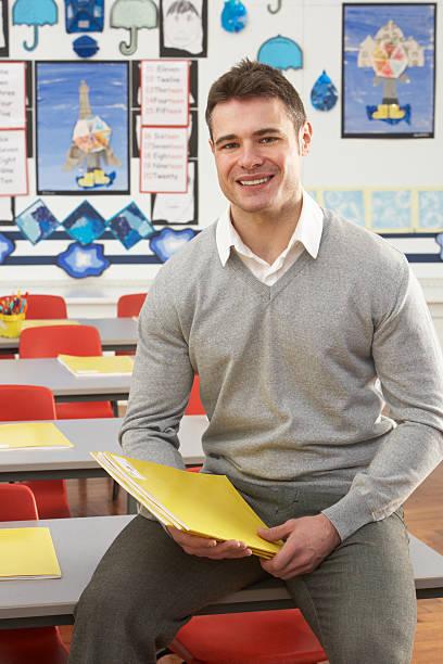Männliche Lehrer Sitzen am Schreibtisch im Klassenzimmer – Foto