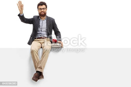 istock Male teacher sitting on a panel and waving 645096380