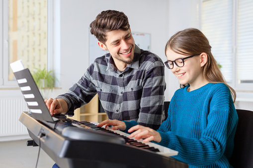 Male Teacher Teaching Piano To Girl In Class Stock Photo - Download Image Now