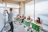 istock Male teacher with face mask teaching a group of students in a high school lesson 1279648007