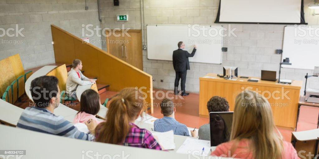 Male teacher with students at the lecture hall stock photo