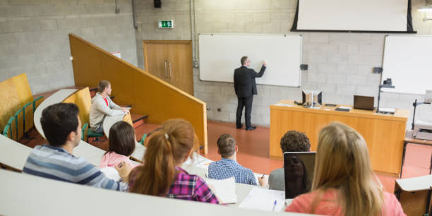 Male teacher with students at the lecture hall Rear view of a male teacher with students at the college lecture hall lecture hall stock pictures, royalty-free photos & images