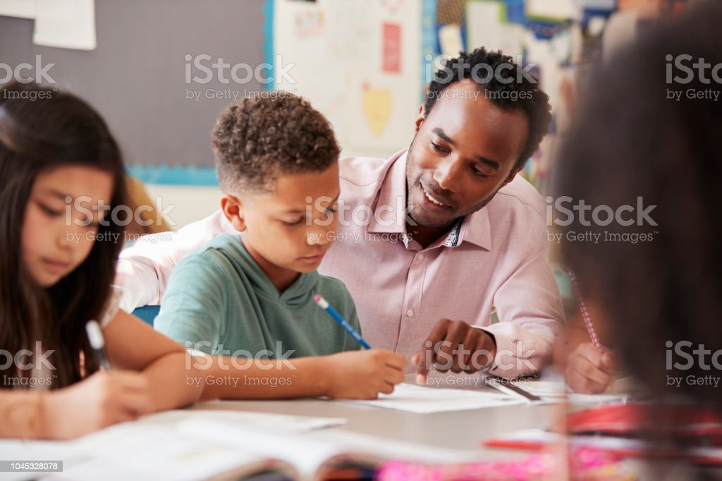 Male teacher working with elementary school boy at his desk royalty-free stock photo