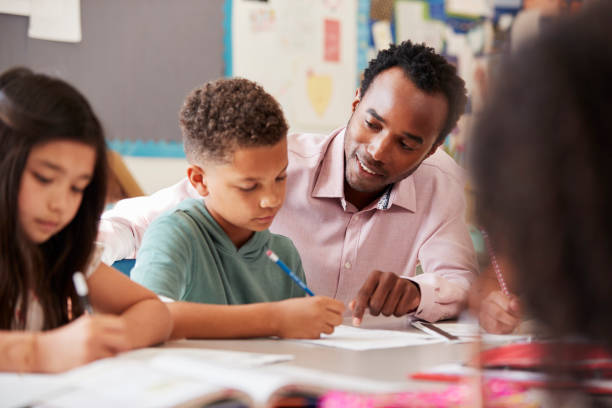 Male teacher working with elementary school boy at his desk stock photo