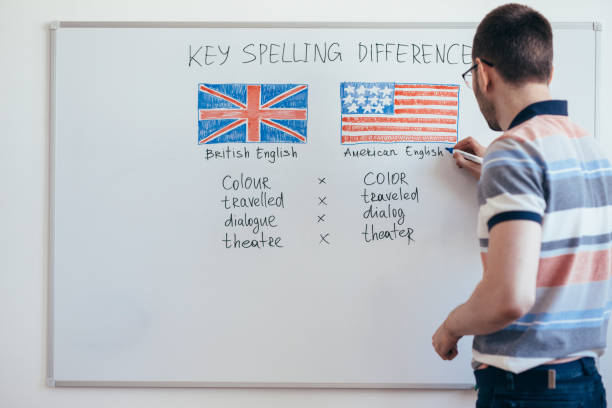 Male teacher writes English grammar on the whiteboard. stock photo