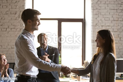 1070271598 istock photo Male team leader handshaking female excited employee congratulating hiring intern 1085713994