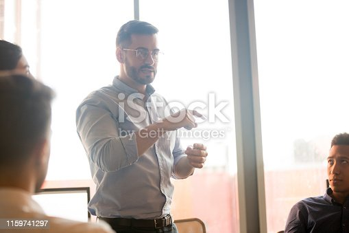 987123762 istock photo Male team leader talk discussing ideas with diverse colleagues 1159741297