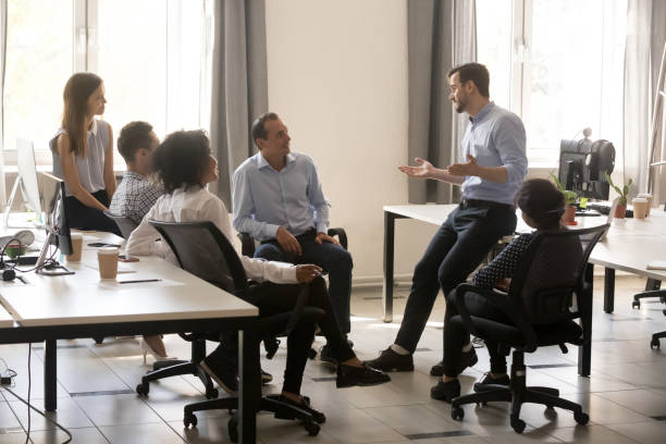 male team leader talking to diverse businesspeople at office meeting - sales stock pictures, royalty-free photos & images