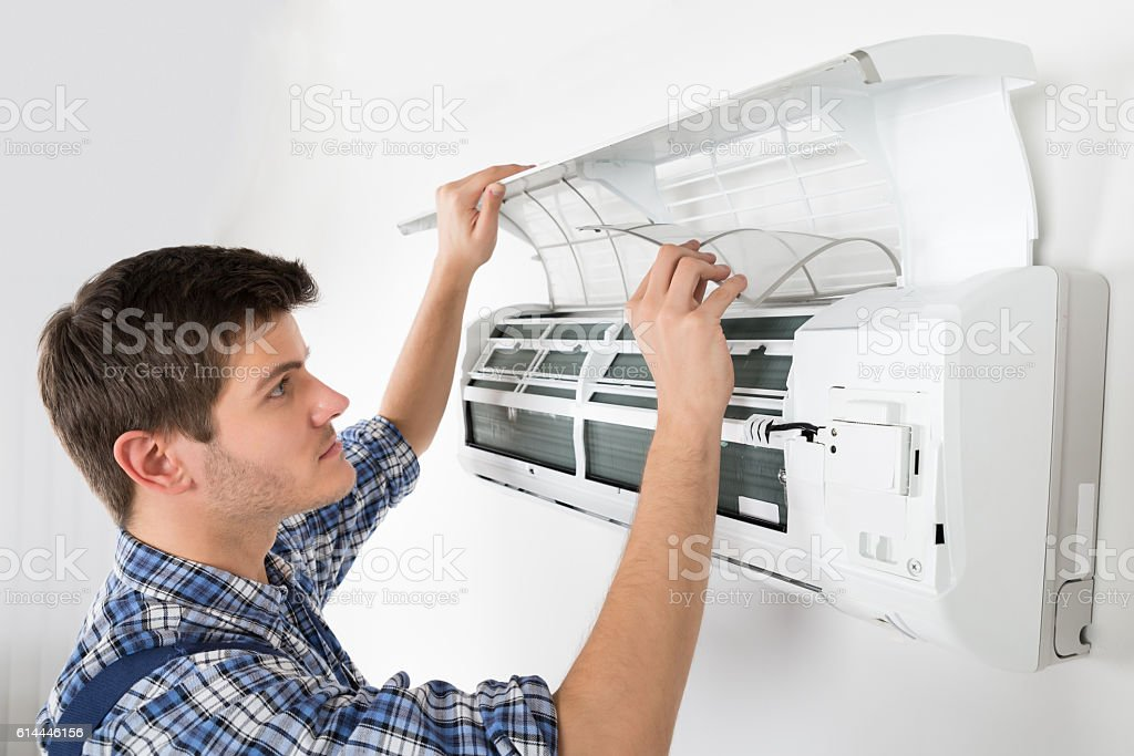 Male Technician Cleaning Air Conditioning System stock photo