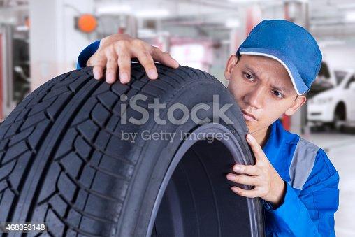 1047558948 istock photo Male technician controls a tire 468393148