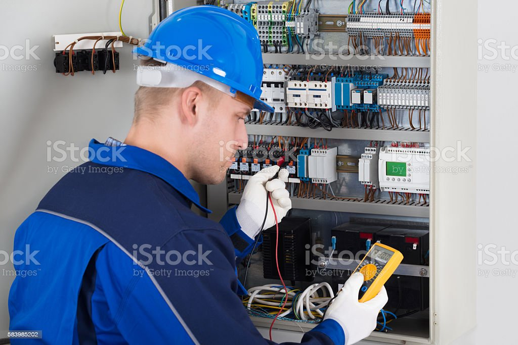 Male Technician Examining Fusebox stock photo