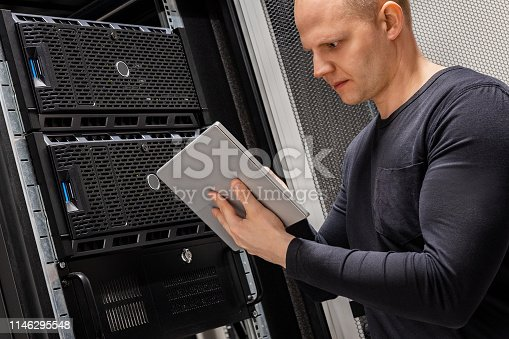 istock Male Technician Holding Digital Tablet Analyzing Servers in Datacenter 1146295548
