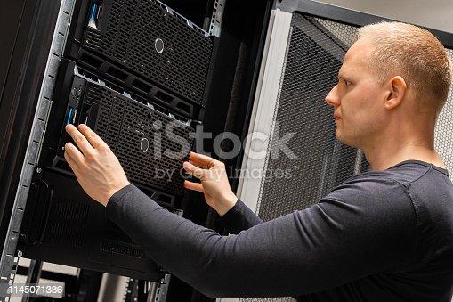istock Male Technician Installing Servers In Enterprise Datacenter for Cloud Hosting 1145071336
