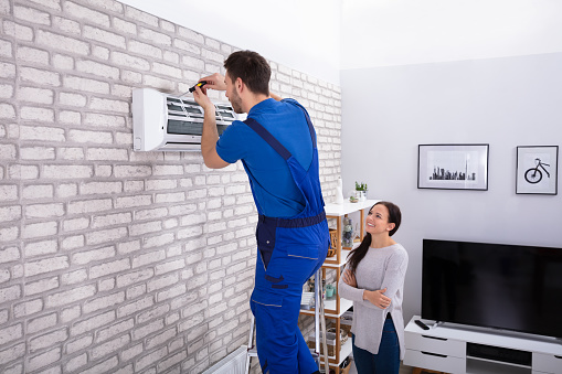 istock Male Technician Repairing Air Conditioner With Screwdriver 1128872922