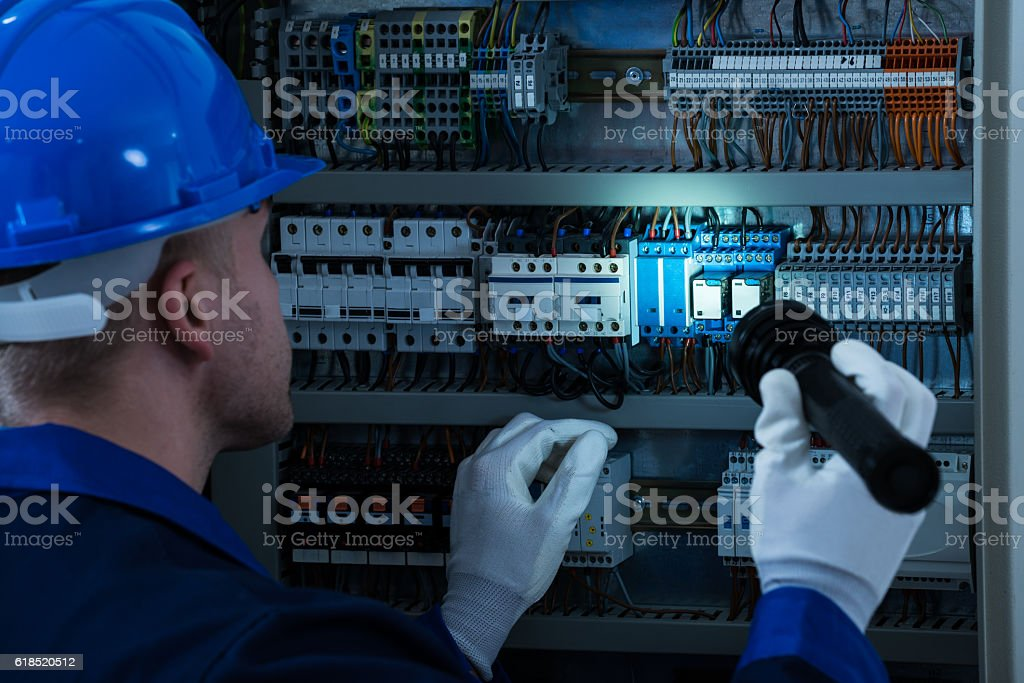 Male Technician Testing Fusebox stock photo