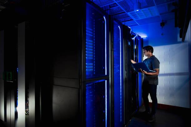 mannelijke technicus werkzaam in server ruimte - datacenter stockfoto's en -beelden