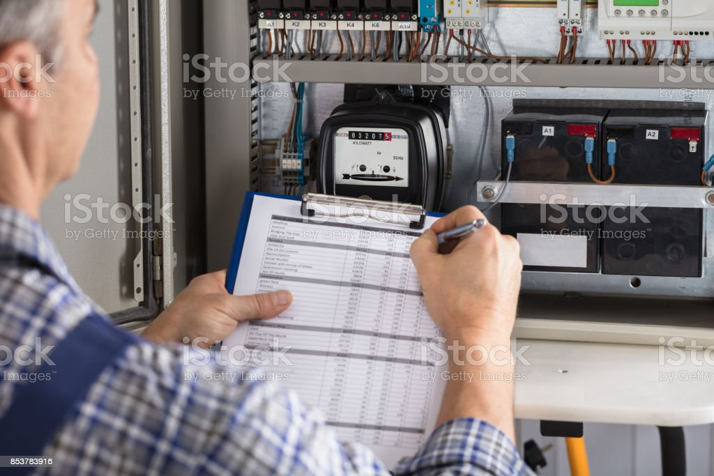 Male Technician Writing Reading Of Meter stock photo