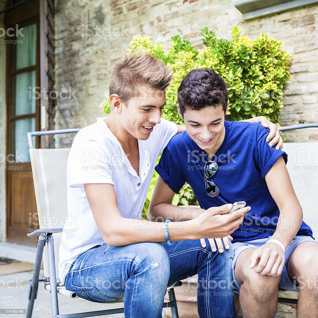 Male Teen Friends Taking Picture Together with a Smartphone royalty-free stock photo