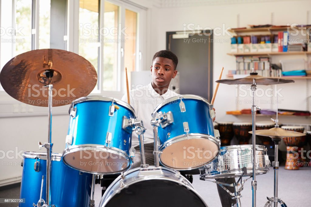 Male Teenage Pupil Playing Drums In Music Lesson stock photo
