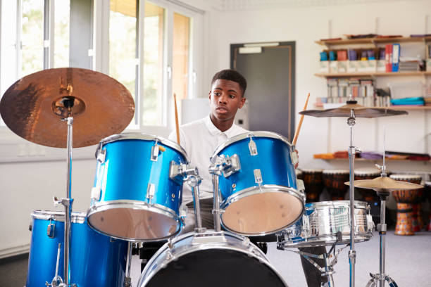 Male Teenage Pupil Playing Drums In Music Lesson Male Teenage Pupil Playing Drums In Music Lesson drum kit stock pictures, royalty-free photos & images
