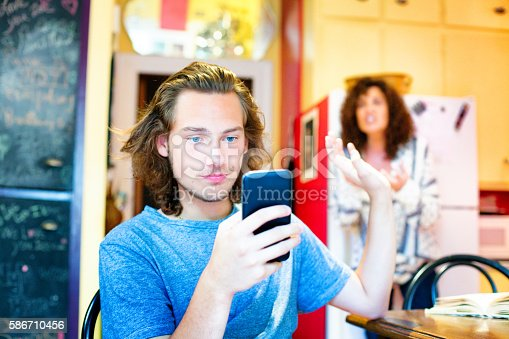istock Male teenager ignoring scolding mom with mobile phone 586710456