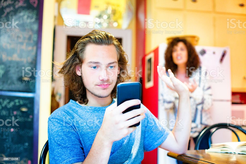 Male teenager ignoring scolding mom with mobile phone stock photo