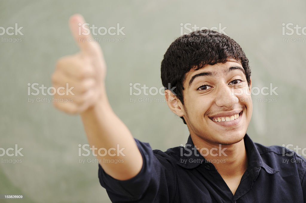 Male teenager student in front of classroom board, thumb up stock photo