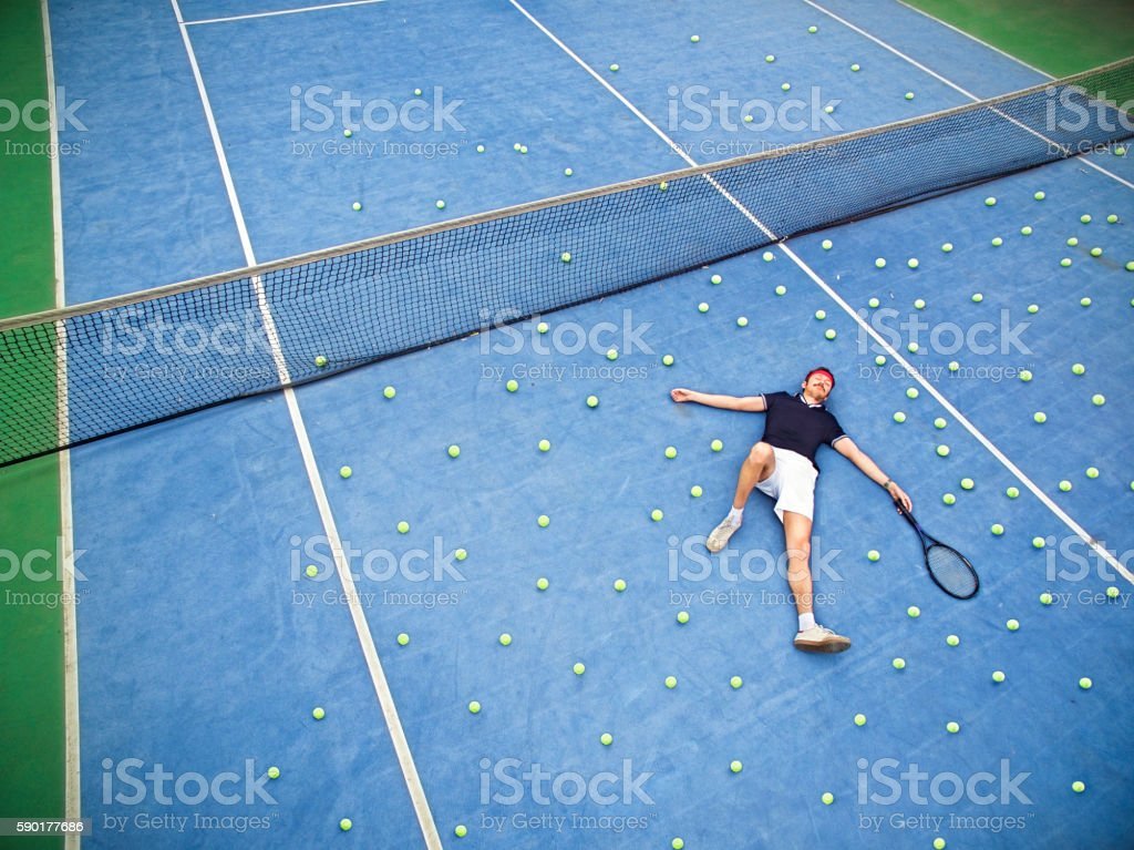 Male tennis player lying on ground - Photo
